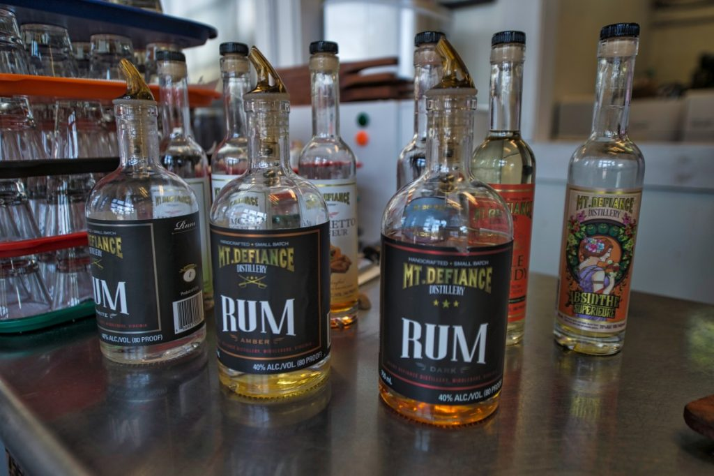 Bottles of rum and absinthe on display in the showroom of the Mt. Defiance Cidery & Distillery in Middleburg. (Douglas Graham/Loudoun Now)