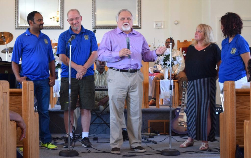 Larry Roeder, center, introduces members of the South Riding Rotary Club as they present a $500 donation to help preserve Prosperity Baptist Church.