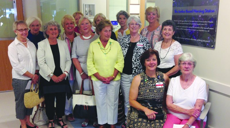 Members of the Ladies Board pose next to the plaque that commemorates the organization's longstanding contributions to Inova Loudoun Hospital and its nurses.  [Inova Loudoun Hospital photo]