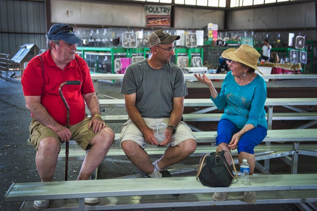 George Callis, Chris Shore and Barbara Callis hang out in the shade during the fair's opening day. (Douglas Graham/Loudoun Now)
