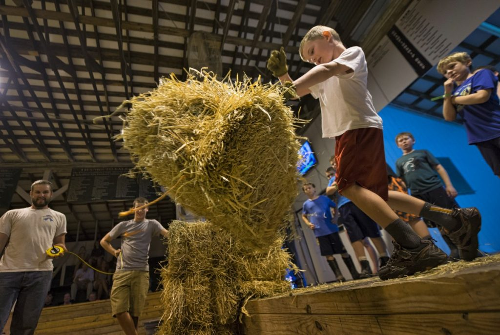 William Lotman, age 6, of Lovettsville, competes in the hay bale toss contest Monday night. (Douglas Graham/Loudoun Now)