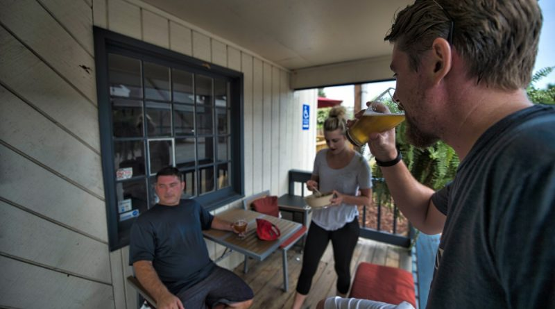Members of the Loud & Brewing Pint Chasers, Patrick Steffens, Beth Dill and Shawn Fitzpatrick, enjoy cold beer on the front porch of Loudoun Brewing Company after their run Sunday morning. Loudoun Brewing Company is the latest brewery to form a running club.  [Douglas Graham/Loudoun Now]