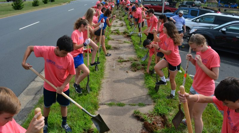 More than 200 campers make short work of edging and clearing the sidewalk at Gwen Thompson Briar Patch Park. (Renss Greene/Loudoun Now)