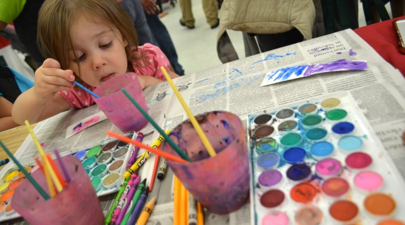 Amelia, 2, settles in at the painting station at the Community Services Night organized by Community Advocates for Education on Monday. (Danielle Nadler/Loudoun Now)