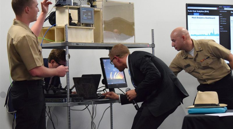 Members of the SUDO Technologies team prepare for a demonstration designed to show how their software can thwart a computer hack aimed at taking control of a ship's engine.