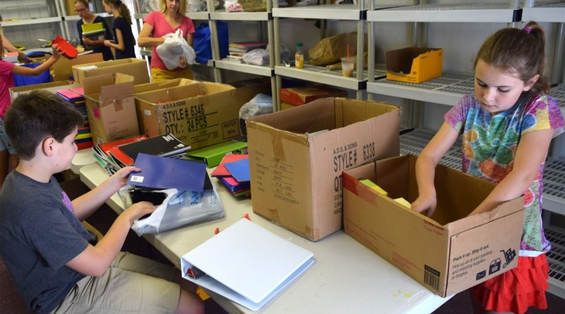 Volunteers at The Salvation Army pack school supplies for students Friday. (Norman K. Styer/Loudoun Now)