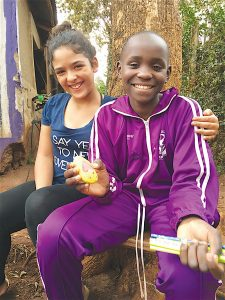 Mia Hattaway poses with Deb Nekesa Kisiangani and one of Cassia's Rocks during a visit to Kenya.  [Courtesy of Naomi Hattaway]