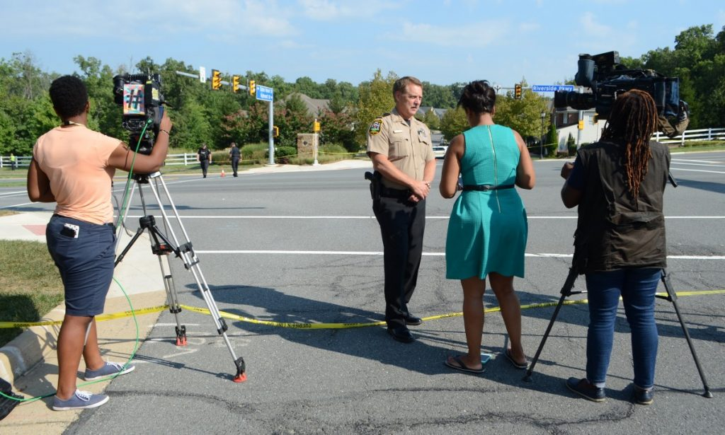 Loudoun Sheriff Mike Chapman takes questions from members of the press. In the background, law enforcement officers investigate the scene of the incident. [Danielle Nadler/Loudoun Now]