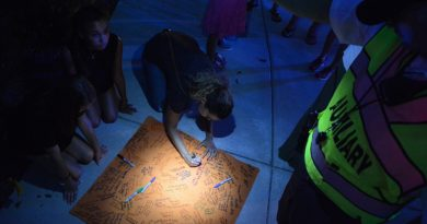 Well-wishers sign a blanket as a Loudoun County Sheriff's Office Auxiliary officer holds a flashlight. (Renss Greene/Loudoun Now)
