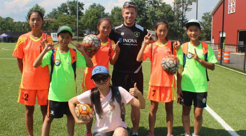 Members of a SportsUnited delegation from China pose on the field at the Evergreen Sportsplex.