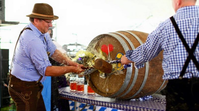 Oktoberfest Chairman Jim McIntyre, left, and Lovettsville Mayor Bob Zoldos tap the keg to kick off last year's festival.  [Alicia Bruce/Love Knot Photography]