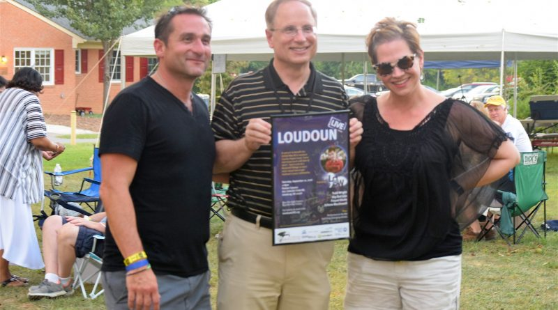 Loudoun Live organizers Ara Bagdasarian, left, and Amy Bobchek present Leesburg Mayor Dave Butler with a promotional poster of the inaugural event at the Paxton campus.