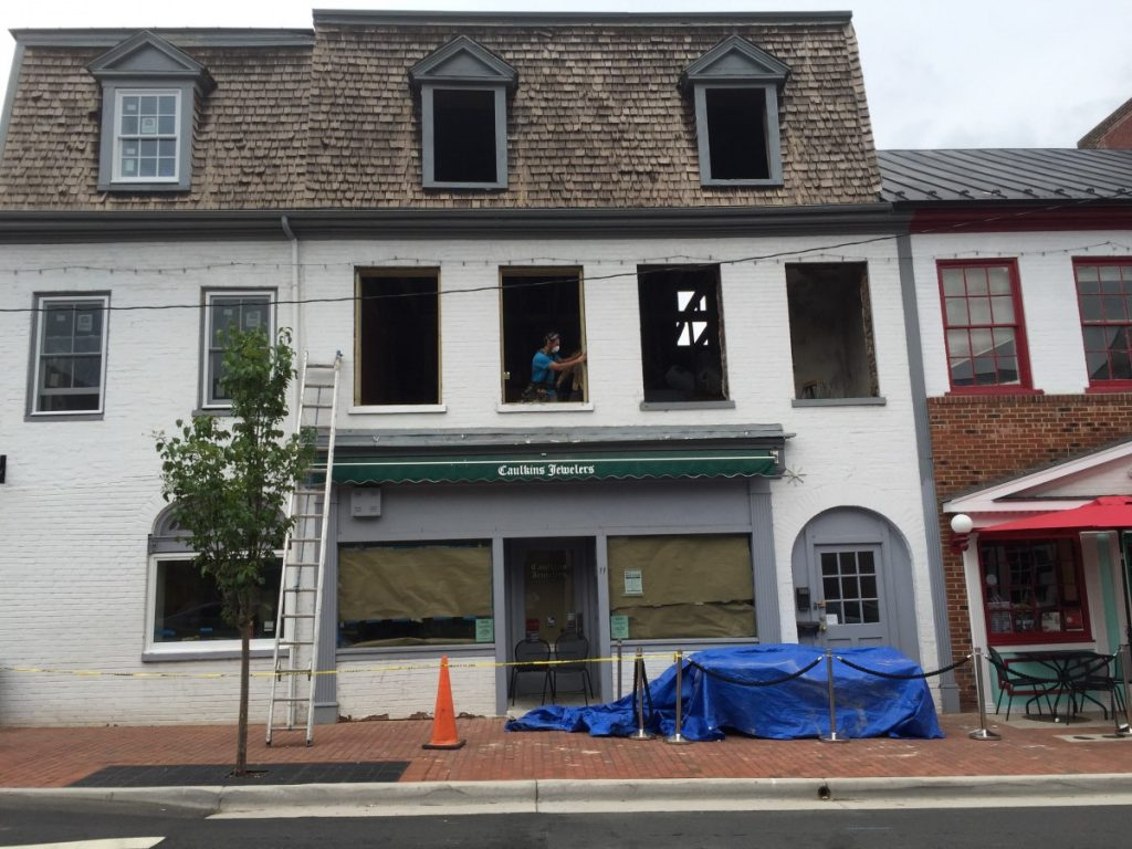 Crews begin work on repairs to the fire-damaged building at 11 S. King St. on Aug. 2.