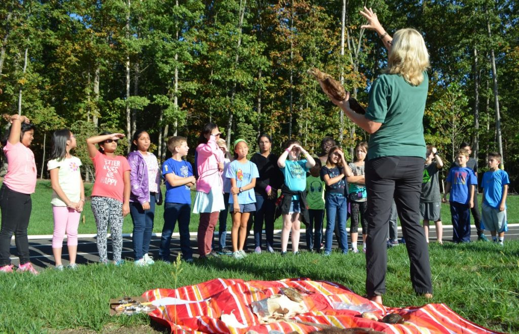Susanne Ortmann, with the Audubon Naturalist Society, leads a lesson on the edge of the Madison's Trust Elementary School campus. [Danielle Nadler/Loudoun Now]