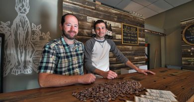 Jay Clement and Ben Baboval of Wild Hare Cider recently launched artisan chocolate company Tightrope Chocolate Co. The owners pose here with cocoa beans and finished chocolate bars in their showroom in Bluemont. [Douglas Graham/Loudoun Now]