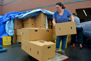 Loudoun Interfaith Relief Executive Director Jennifer Montgomery loads boxes of food onto a cart. (Renss Greene/Loudoun Now)