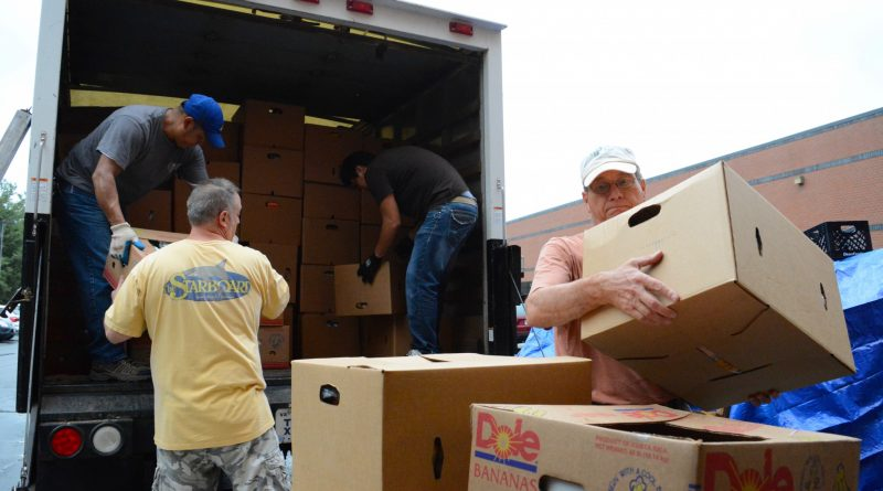 Interfaith volunteers unload truckloads of donated food from the Purcellville Food Lion. (Renss Greene/Loudoun Now)