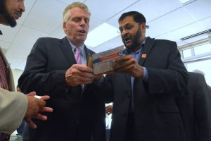 ADAMS Vice President Sohel Ahmed gives Governor Terry McAuliffe a card with some of ADAMS' campaigns to encourage Muslims to vote. (Renss Greene/Loudoun Now)