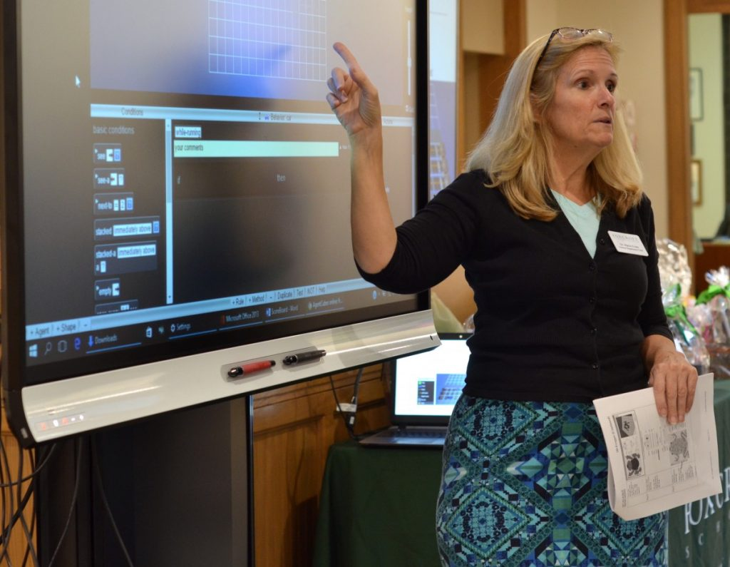 Foxcroft STEM Department Chair Maria Evans guides middle school girls through a lesson in coding. [Danielle Nadler/Loudoun Now]