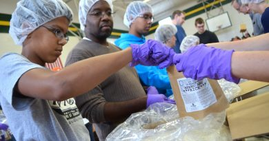Father-son team Christopher and Dave Howard, of Leesburg, joined more than 350 volunteers at Douglass School Sunday to package 15,000 meals for hungry Loudoun families. [Danielle Nadler/Loudoun Now]