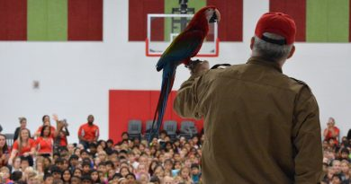 Lola, the macaw, greets students at Madison's Trust Elementary School, where the mascot is the Mighty Macaws. [Danielle Nadler/Loudoun Now]