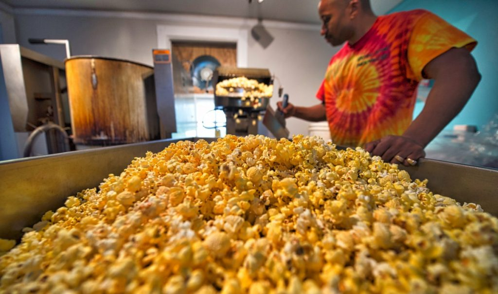 Popcorn Monkey owner Deltone Moore pops a fresh batch of popcorn in the kitchen where he cooks up a huge selection of creative flavors.  [Douglas Graham/Loudoun Now]