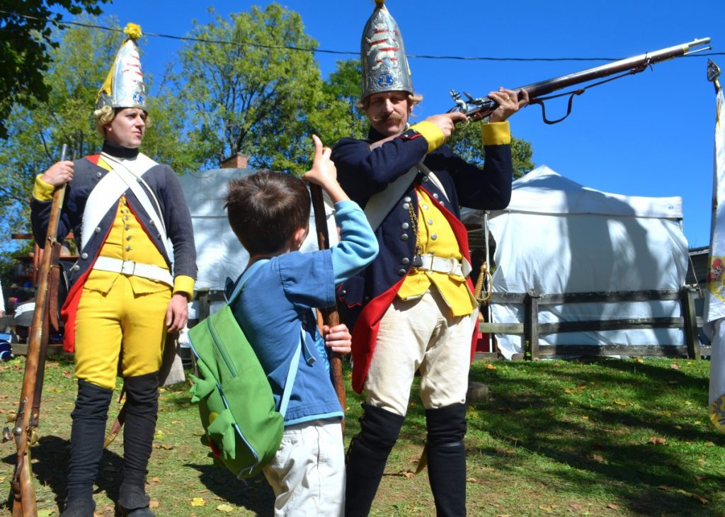 Men dressed as Hessian soldiers give a young boy a lesson in loading ammunition at the Waterford Fair on Sunday. [Danielle Nadler/Loudoun Now]