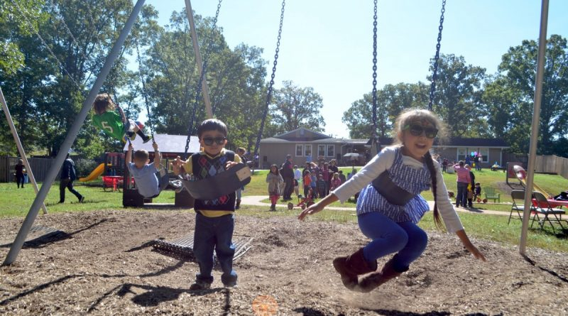 From left, 3-year-old William and 6-year-old Ellie break in the swings at the new YMCA Loudoun County Youth Development Center on Saturday. [Danielle Nadler/Loudoun Now]