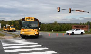 Buses carrying Tuscarora High School students leave the campus in Leesburg as law enforcement officers investigate a bomb threat at the school.