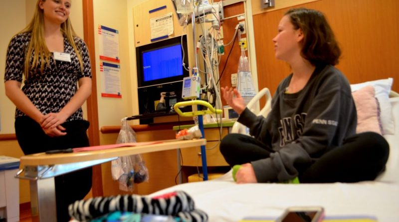 Grace Boyles, a senior at Stone Bridge High School, chats with Shannon Lyons, an 18-year-old patient at Inova Loudoun Hospital during the annual Job for a Day program. Grace shadowed nurses in the hospital's pediatrics department. [Danielle Nadler/Loudoun Now]