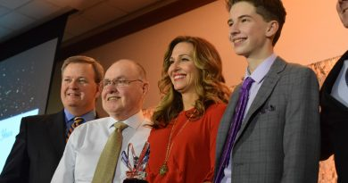 The Wellness Collection founder Susan McCormick is flanked by her father and her son as she accepts the Small Business of the Year award.