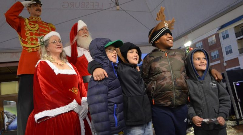 Friends Alex, Chris, Jordan and Hunter pose with Santa, Mrs. Claus and a toy soldier at the Village at Leesburg.  [Danielle Nadler/Loudoun Now]