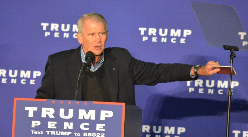 Oliver North holds a copy of the U.S. Constitution during his speech at the Nov. 6 Trump rally near Leesburg. [Norman K. Styer/Loudoun Now]