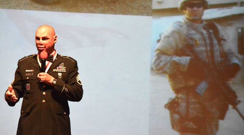 As he delivers the keynote address during the Salute Our Heroes dinner in Lansdowne, Staff Sergeant Shilo Harris stands in front of a photo of himself taken before he was badly injured in an IED attack near Baghdad that killed three members of his unit