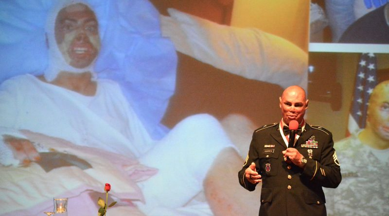 As he delivers the keynote address during the Salute Our Heroes dinner in Lansdowne, Staff Sergeant Shilo Harris stands in front of a photo of himself recovering from injures suffered in an IED attack near Baghdad that killed three members of his unit.