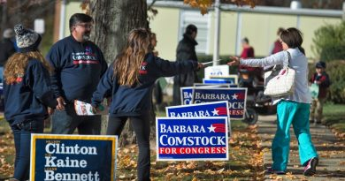 Voters at the Round Hill school pass by the gauntlet of sign-wielding poll workers as they head into vote. (Douglas Graham/Loudoun Now)