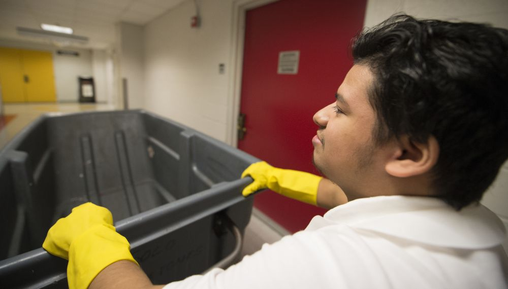 Guillermo Aviles, a Project SEARCH intern, recycles packaging at the National Conference Center. [Douglas Graham/Loudoun Now]
