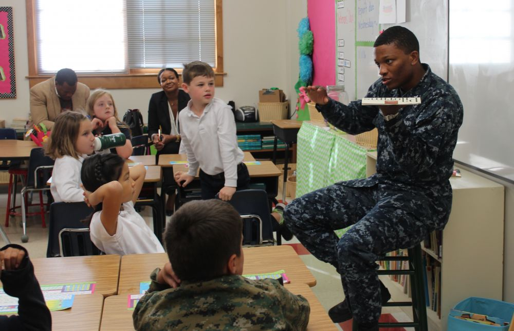 Alex Charles, chief petty officer in the U.S. Navy, speaks with his little sister's second-grade class at Loudoun Country Day School. [Amy Warner/Loudoun Country Day School]