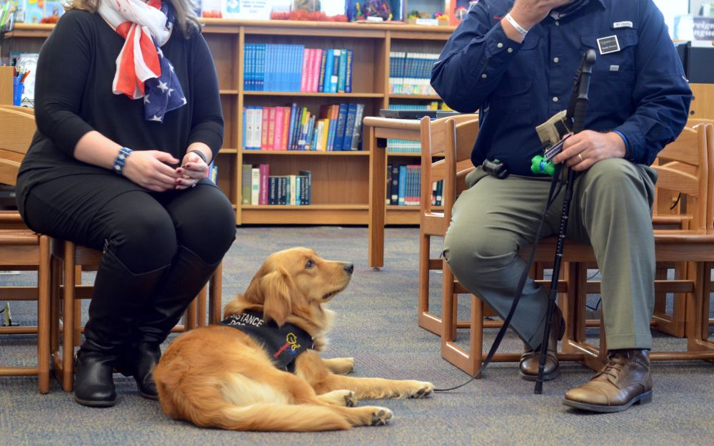 Shilo sits with her handler, military veteran Randy Powers, at Loudoun Country Day School's Veterans Day program Friday. [Danielle Nadler/Loudoun Now]