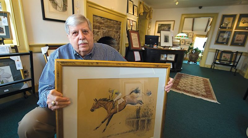 William Teringo poses with an original signed watercolor by Louis Calude from the 1930s in his downtown Leesburg gallery. [Douglas Graham/Loudoun Now]