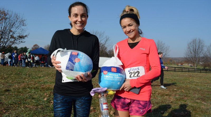 Noel Blakeney and Jennifer Nash, both of Leesburg, go home with frozen turkeys they won as prizes for their run at the Freeze Your Gizzard Cross Country 5K. Blakeney finished second in her age group; Nash finished first in hers. (Renss Greene/Loudoun Now)