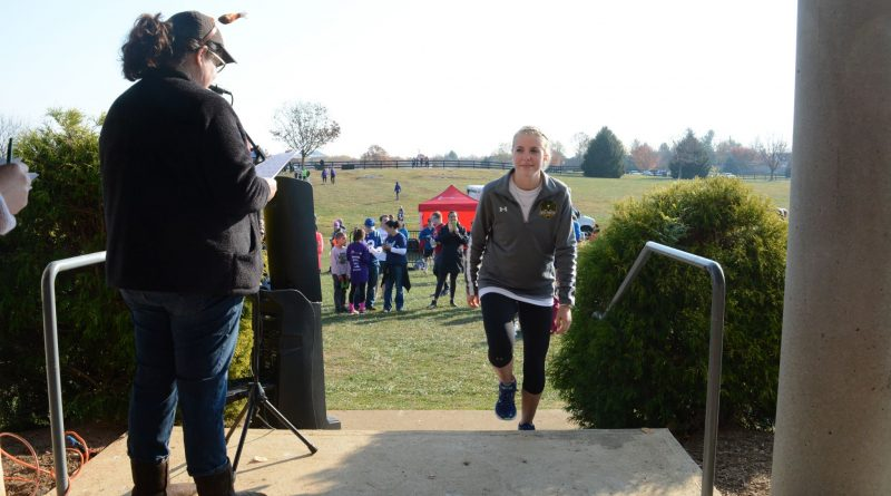 One of the winners of the Freeze Your Gizzard Cross Country 5K comes to the stage to accept an award and a high-five from Loudoun Hunger Relief Executive Director Jennifer Montgomery. (Renss Greene/Loudoun Now)