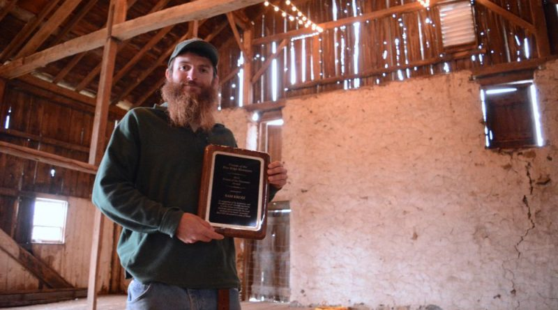 Sam Kroiz holds his 2016 Friend of the Mountain Award in the family's barn at Georges Mill Farm near Lovettsville. (Renss Greene/Loudoun Now)
