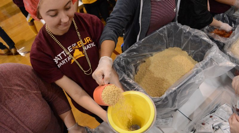 Broad Run High School students pour rice into a funnel to fill meal bags. (Renss Greene/Loudoun Now)