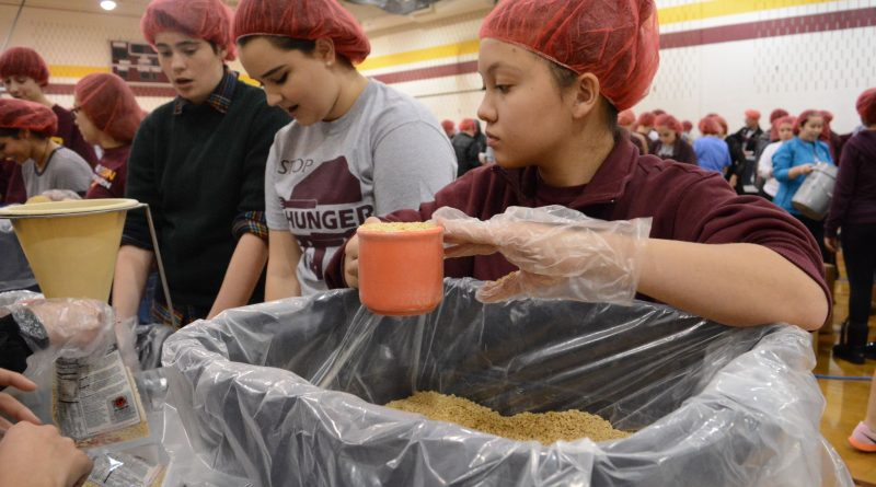 A Broad Run High School student measures a scoop of rice for a meal bag. (Renss Greene/Loudoun Now)