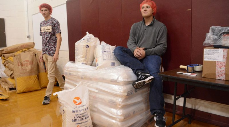 Students lounge on a pallet of rice, distributing refills to meal bag assembly stations that run out. (Renss Greene/Loudoun Now)