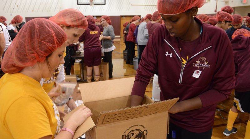Broad Run High School pack meal bags into boxes to ship out. (Renss Greene/Loudoun Now)