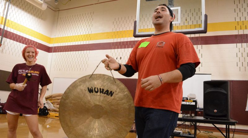 Stop Hunger Now Assistant Program Manager Alex Hart announces 10,000 meals packed—halfway through the day's work—with a cymbal. (Renss Greene/Loudoun Now)