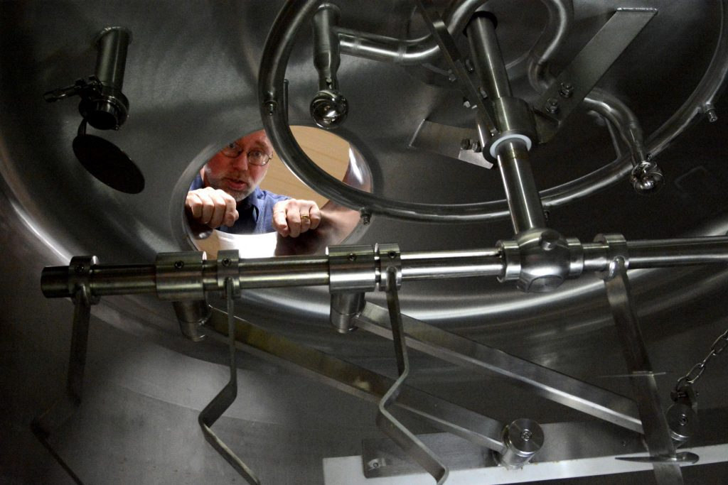 Roger Knoell looks into the new mash tun, part of his new, greatly expanded brewing operation. (Renss Greene/Loudoun Now)
