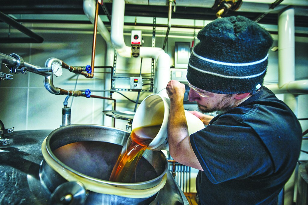 Nassim Sultan adds honey from Loudoun to a batch of root beer at Lost Rhino Brewing Company in Ashburn. (Photo By Douglas Graham/Loudoun Now)
